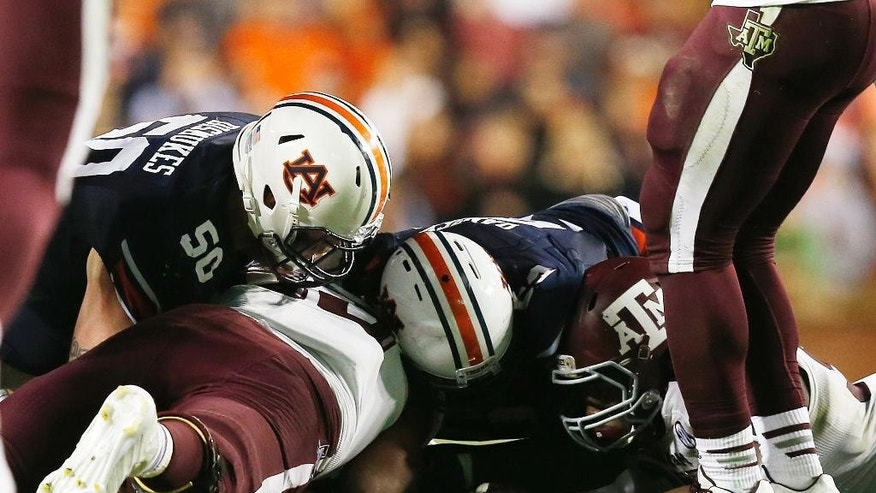 Auburn offensive lineman Reese Dismukes (50) fumbles the ball with a recovery by Texas A&M defensive lineman Alonzo Williams (83) during the second half of an NCAA college football game Saturday, Nov. 8, 2014, in Auburn, Ala. (AP Photo/Brynn Anderson)