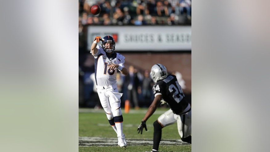 Denver Broncos quarterback Peyton Manning (18) passes the ball over Oakland Raiders cornerback Charles Woodson (24) during the third quarter of an NFL football game in Oakland, Calif., Sunday, Nov. 9, 2014. (AP Photo/Ben Margot)
