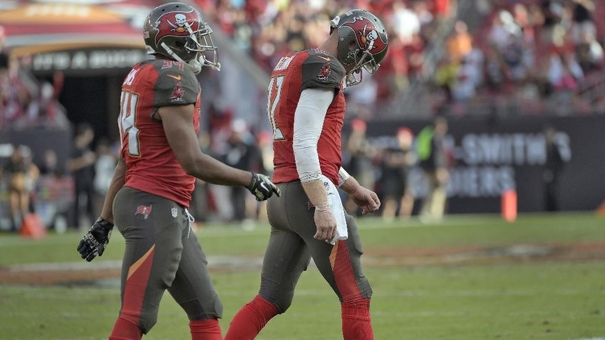 Tampa Bay Buccaneers quarterback Josh McCown (12) and running back Charles Sims (34) leave the field during the fourth quarter of an NFL football game against the Atlanta Falcons on Sunday, Nov. 9, 2014, in Tampa, Fla. (AP Photo/Phelan M. Ebenhack)