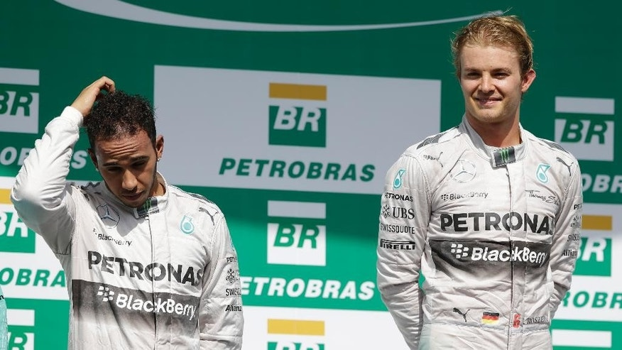 Mercedes driver Nico Rosberg, of Germany, right and teammate Lewis Hamilton, of Britain, stand on the podium for Formula One Brazilian Grand Prix at the Interlagos race track in Sao Paulo, Brazil, Sunday, Nov. 9, 2014. Rosberg fended off a strong charge by Hamilton to win the Brazilian Grand Prix on Sunday, closing in on his Mercedes teammate in the Formula One title race. (AP Photo/Ricardo Mazalan)