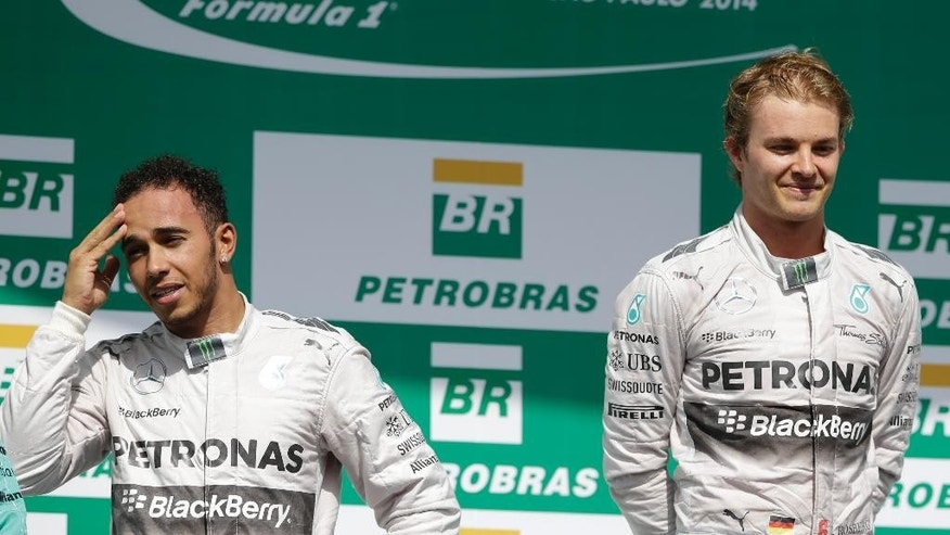 Mercedes driver Nico Rosberg of Germany, right, and teammate Lewis Hamilton of Britain, stand on the podium after the Formula One Brazilian Grand Prix at the Interlagos race track in Sao Paulo, Brazil, Sunday, Nov. 9, 2014. Rosberg fended off a strong charge by Hamilton to win the Brazilian Grand Prix on Sunday, closing in on his Mercedes teammate in the Formula One title race. (AP Photo/Ricardo Mazalan)