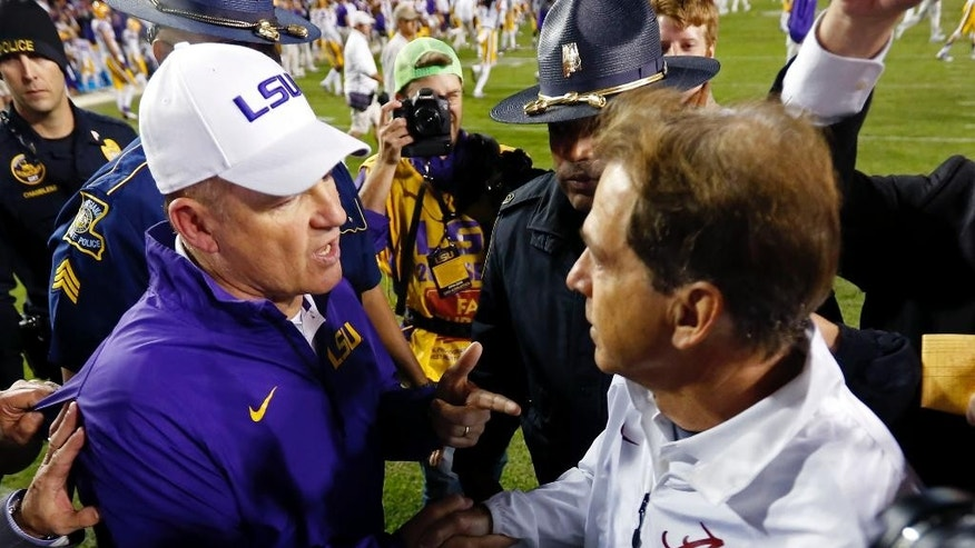LSU coach Les Miles, left, shakes hands with Alabama coach Nick Saban after an NCAA college football game in Baton Rouge, La., Saturday, Nov. 8, 2014. Alabama won in overtime, 20-13. (AP Photo/Jonathan Bachman)