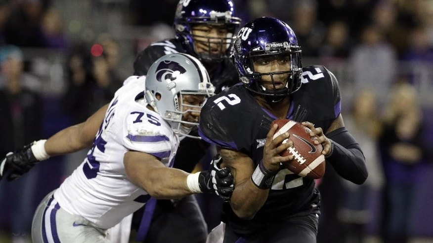 TCU quarterback Trevone Boykin (2) eludes Kansas State defensive end Jordan Willis (75) during the second half of an NCAA college football game Saturday, Nov. 8, 2014, in Fort Worth, Texas. TCU won 41-20. (AP Photo/LM Otero)