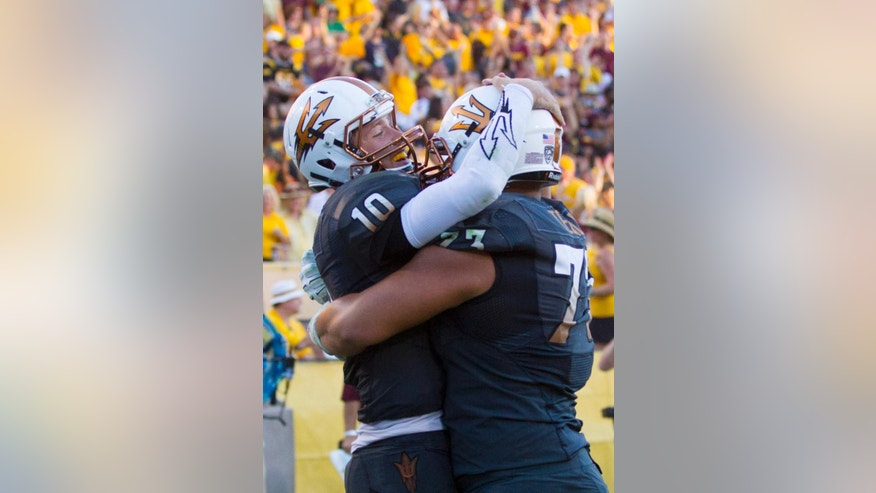 Arizona State quarterback Taylor Kelly, left, celebrates with teammate Vi Teofilo after Taylor scored a touchdown in the fourth quarter against Notre Dame in an NCAA college football game Saturday, Nov. 8, 2014 at Sun Devil Stadium in Tempe, Ariz. (AP Photo/The Arizona Republic, Cheryl Evans)  MARICOPA COUNTY OUT; MAGS OUT; NO SALES