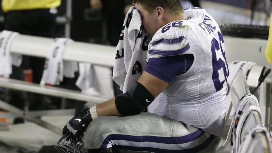 Kansas State offensive lineman B.J. Finney (66) sits alone on the bench during the  fourth quarter of an NCAA college football game against TCU, Saturday, Nov. 8, 2014, in Fort Worth, Texas. TCU won 41-20. (AP Photo/LM Otero)