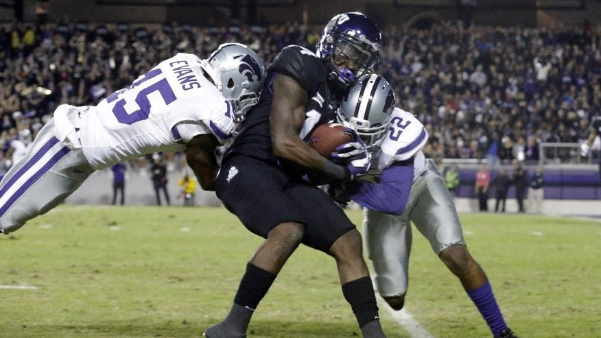 TCU wide receiver David Porter, center, is tackled by Kansas State defensive backs Dante Barnett (22) and Randall Evans (15) after making a catch during the first quarter of an NCAA college football game Saturday, Nov. 8, 2014, in Fort Worth, Texas. (AP Photo/LM Otero)