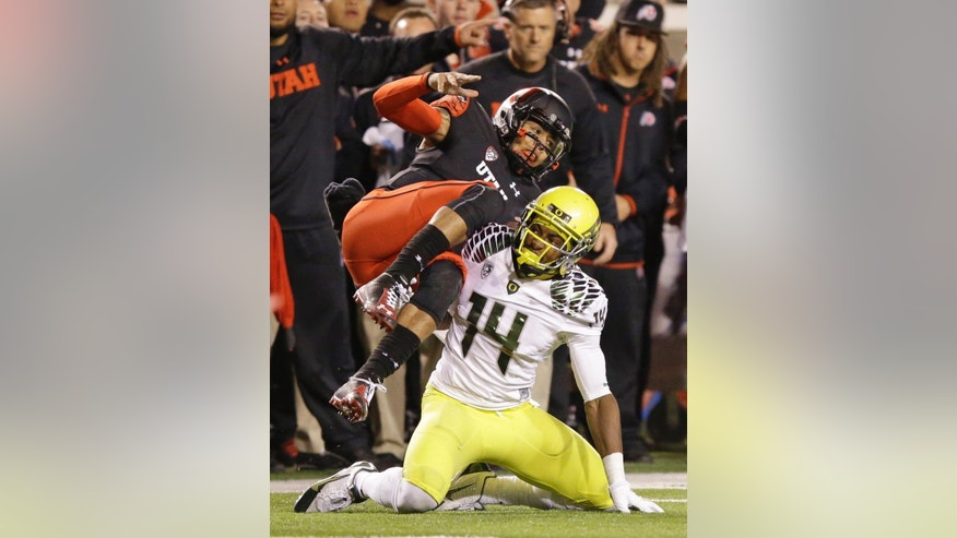 Utah quarterback Kendal Thompson (1) is tackled by Oregon defensive back Ifo Ekpre-Olomu (14) during the first quarter in an NCAA college football game Saturday, Nov. 8, 2014, in Salt Lake City. (AP Photo/Rick Bowmer)
