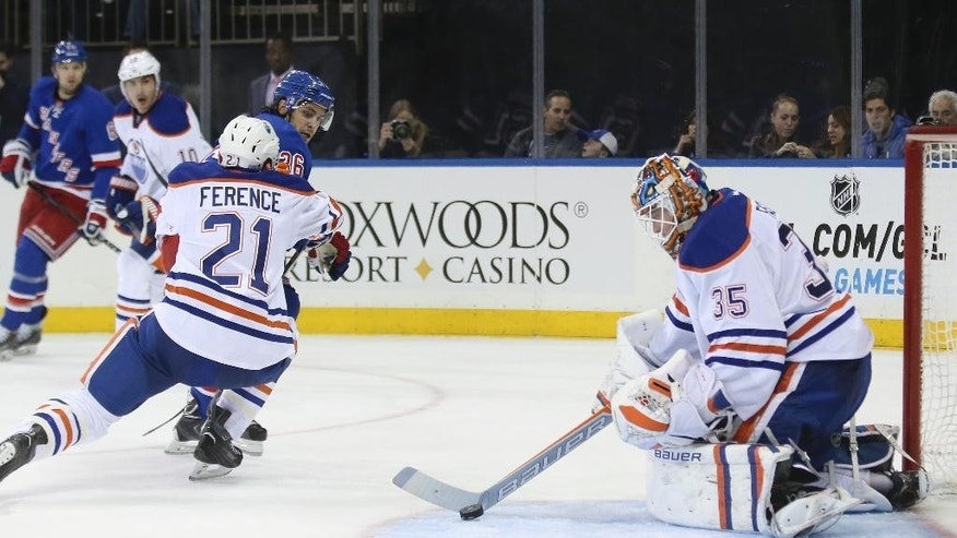 Edmonton Oilers goalie Viktor Fasth (35) makes a save on a shot by New York Rangers right wing Mats Zuccarello (36) as Edmonton Oilers defenseman Andrew Ference (21) defends during the second period of an NHL hockey game at Madison Square Garden, Sunday, Nov. 9, 2014, in New York. (AP Photo/John Minchillo)