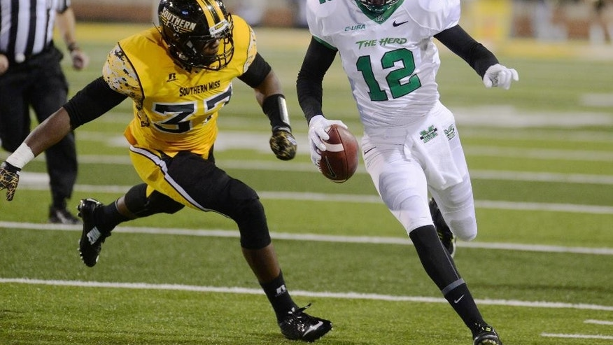 Marshall quarterback Rakeem Cato (12) runs past Southern Mississippi linebacker Alan Howze (37) for a touchdown in the first half during a NCAA college football game in Hattiesburg, Miss., Saturday, Nov. 8, 2014. (AP Photo/Steve Coleman)
