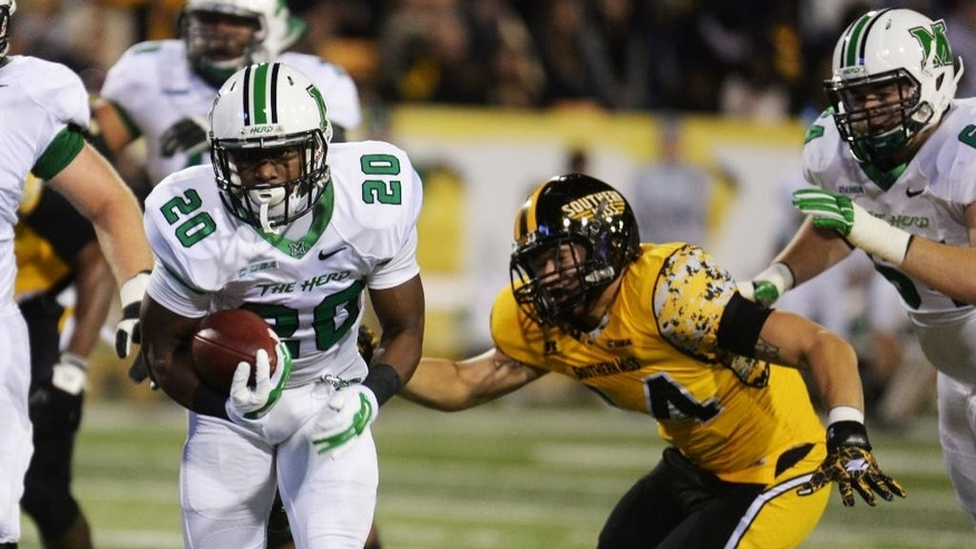 Marshall running back Steward Butler (20) runs past Southern Mississippi linebacker Terrick Wright (14) for a touchdown in the first half of their NCAA college football game in Hattiesburg, Miss., Saturday, Nov. 8, 2014. (AP Photo/Steve Coleman)
