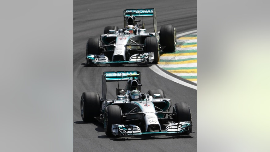 Mercedes driver Nico Rosberg, of Germany, front, and teammate Lewis Hamilton, of Britain, steer their cars during the Formula One Brazilian Grand Prix at the Interlagos race track in Sao Paulo, Brazil, Sunday, Nov. 9, 2014. (AP Photo/Silvia Izquierdo)
