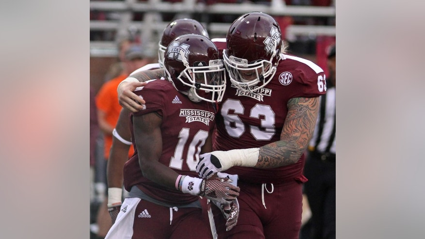 Mississippi State's Dillon Day (63) congratulates Brandon Holloway (10) following his first-half touchdown during an NCAA college football game against Tennessee-Martin in Starkville, Miss., Saturday, Nov. 8, 2014. Mississippi State won 45-16. (AP Photo/Jim Lytle)