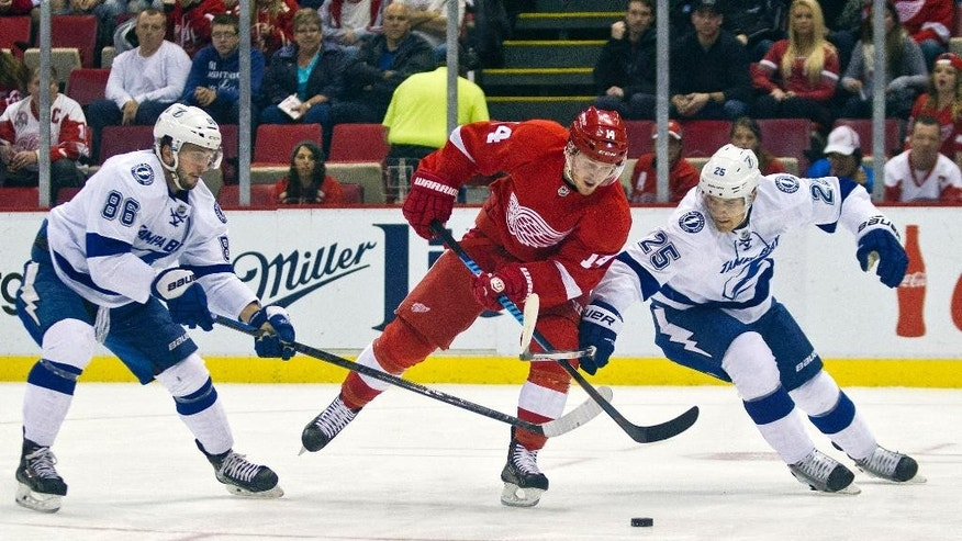 Tampa Bay Lightning forward Nikita Kucherov (86), of Russia, and defenseman Matthew Carle (25) vie for the puck with Detroit Red Wings forward Gustav Nyquist (14), of Sweden, during the first period of an NHL hockey game in Detroit, Mich., Sunday, Nov. 9, 2014. (AP Photo/Tony Ding)