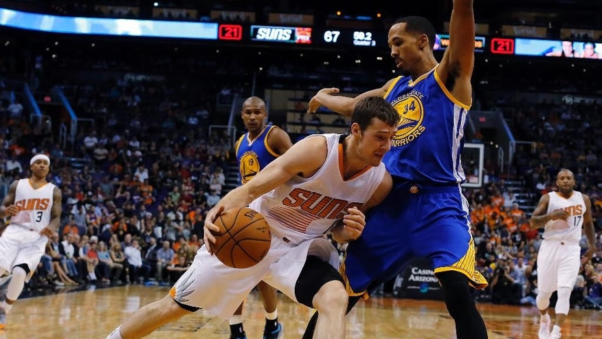 Phoenix Suns guard Goran Dragic (1) drives on Golden State Warriors guard Shaun Livingston (34) during the second half of an NBA basketball game, Sunday, Nov. 9, 2014, in Phoenix. The Suns won 107-95. (AP Photo/Rick Scuteri)
