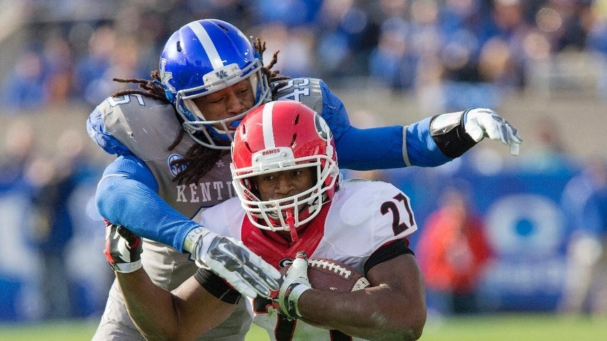 Georgia running back Nick Chubb gets wrapped up by Kentucky linebacker Josh Forrest during the second half of an NCAA college football game at Commonwealth Stadium in Lexington, Ky., Saturday, Nov. 8, 2014. Georgia beat Kentucky 63-31. (AP Photo/David Stephenson)