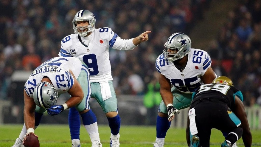 Dallas Cowboys quarterback Tony Romo (9) makes a call against the Jacksonville Jaguars during the NFL football game at Wembley Stadium, London, Sunday, Nov. 9, 2014.  (AP Photo/Matt Dunham)