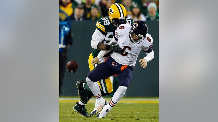 Green Bay Packers outside linebacker Julius Peppers (56) trips the ball as he tackles Chicago Bears quarterback Jay Cutler (6) during the first half of an NFL football game Sunday, Nov. 9, 2014, in Green Bay, Wis. (AP Photo/Mike Roemer)