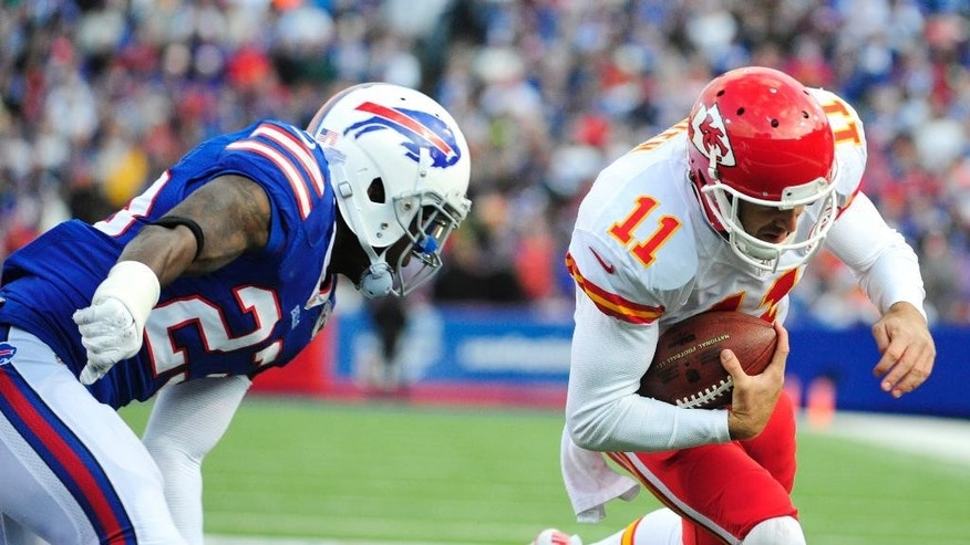 El quarterback Alex Smith (derecha) de los Chiefs de Kansas City se prepara para recibir un golpe de Aaron Williams de los Bills de Buffalo, el domingo 9 de noviembre de 2014. (AP Foto/Gary Wiepert)