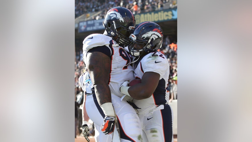 Denver Broncos running back C.J. Anderson, right, celebrates with defensive tackle Terrance Knighton after scoring on a 51-yard touchdown reception against the Oakland Raiders during the second quarter of an NFL football game in Oakland, Calif., Sunday, Nov. 9, 2014. (AP Photo/Marcio Jose Sanchez)