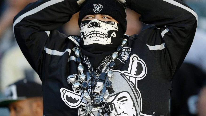 An Oakland Raiders fan watches from his seat during the fourth quarter of an NFL football game between the Raiders and the Denver Broncos in Oakland, Calif., Sunday, Nov. 9, 2014. (AP Photo/Ben Margot)