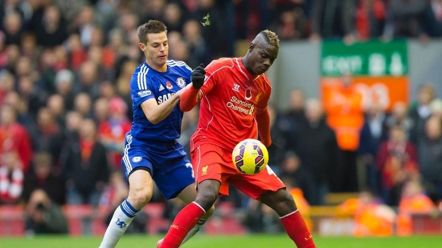 Liverpool's Mario Balotelli, center, fights for the ball against Chelsea's Cesar Azpilicueta during the English Premier League soccer match between Liverpool and Chelsea at Anfield Stadium, Liverpool, England, Saturday Nov. 8, 2014. (AP Photo/Jon Super)