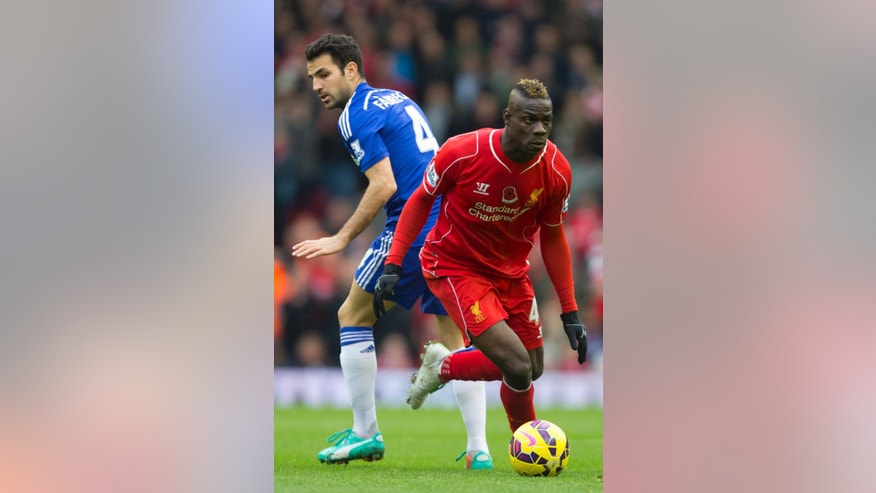 Liverpool's Mario Balotelli, right, keeps the ball from Chelsea's Cesc Fabregas during the English Premier League soccer match between Liverpool and Chelsea at Anfield Stadium, Liverpool, England, Saturday Nov. 8, 2014. (AP Photo/Jon Super)