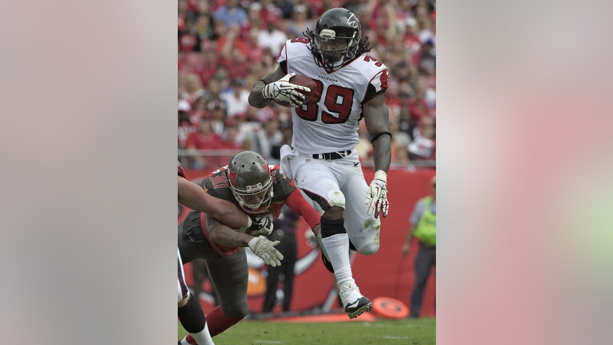 Atlanta Falcons running back Steven Jackson (39) leaps away from Tampa Bay Buccaneers free safety Bradley McDougald (30) for a 1-yard touchdown run during the first quarter of an NFL football game Sunday, Nov. 9, 2014, in Tampa, Fla. (AP Photo/Phelan Ebenhack)