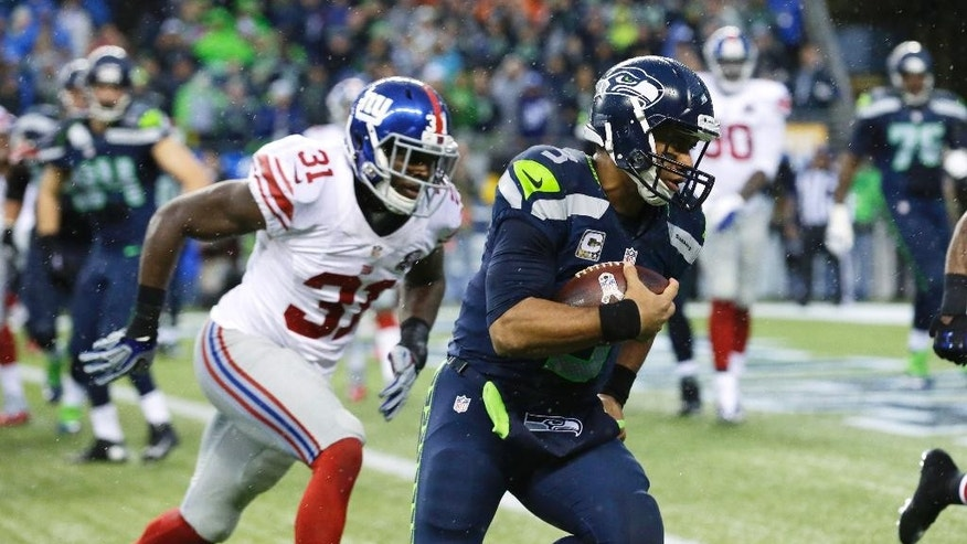 Seattle Seahawks' Marshawn Lynch is tackled by New York Giants middle linebacker Jameel McClain, left, after losing his helmet in the second half of an NFL football game, Sunday, Nov. 9, 2014, in Seattle. The Seahawks beat the Giants, 38-17. (AP Photo/Scott Eklund)