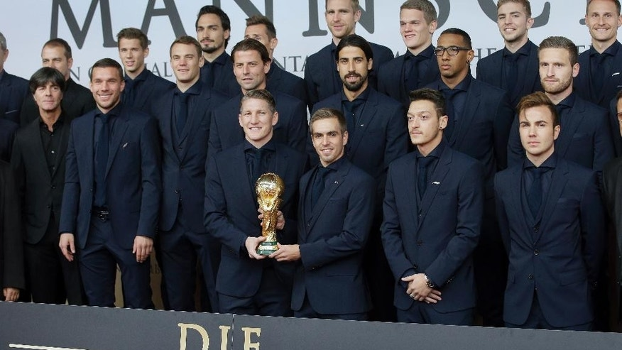 The players of the German national soccer team pose with the World Cup trophy as they arrive for the premiere of the movie 'Die Mannschaft' (The Team) in Berlin, Germany, Monday, Nov. 10, 2014. (AP Photo/Michael Sohn)
