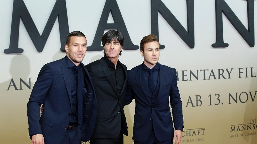 The manager of the German national soccer team Joachim Loew, center, and the players Lukas Podolski, left, and Mario Goetze, right,  pose for the media as they arrive for the premiere of the movie 'Die Mannschaft' (The Team) in Berlin, Germany, Monday, Nov. 10, 2014. (AP Photo/Michael Sohn)