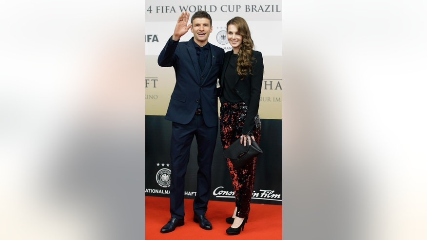 Thomas Mueller, player of the German national soccer team, and his wife Lisa pose for the media as they arrive for the premiere of the movie 'Die Mannschaft' (The Team) in Berlin, Germany, Monday, Nov. 10, 2014. (AP Photo/Michael Sohn)