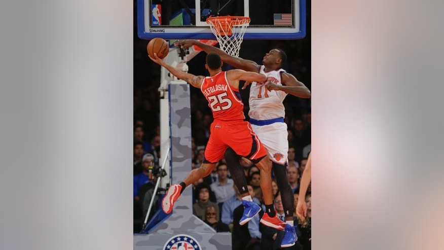Atlanta Hawks' Thabo Sefolosha (25) drives past New York Knicks' Samuel Dalembert (11) during the first half of an NBA basketball game Monday, Nov. 10, 2014, in New York.  (AP Photo/Frank Franklin II)