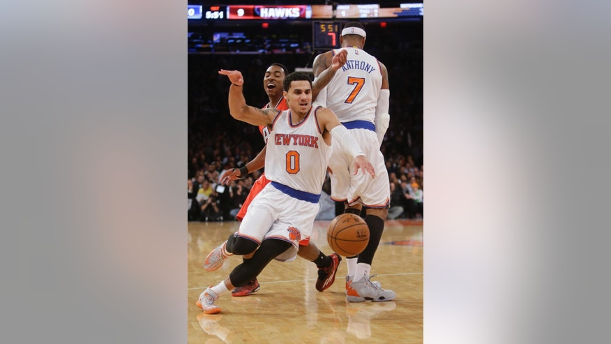New York Knicks' Shane Larkin (0) uses a pick set by Carmelo Anthony (7) as Atlanta Hawks' Jeff Teague  chases him during the first half of an NBA basketball game Monday, Nov. 10, 2014, in New York.  (AP Photo/Frank Franklin II)