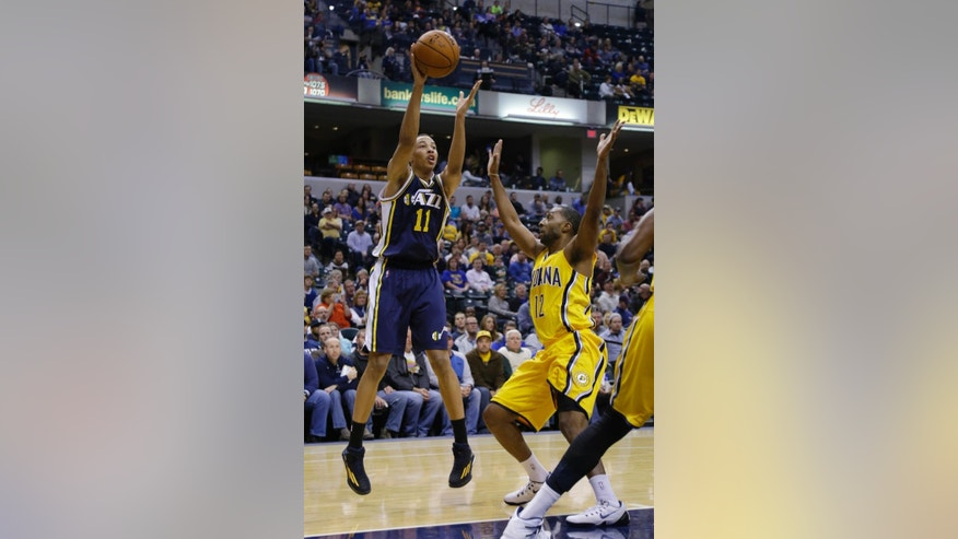 Utah Jazz guard Dante Exum, left, makes a pass over Indiana Pacers guard A.J. Price during the first half of an NBA basketball game in Indianapolis, Monday, Nov. 10, 2014. (AP Photo/Michael Conroy)
