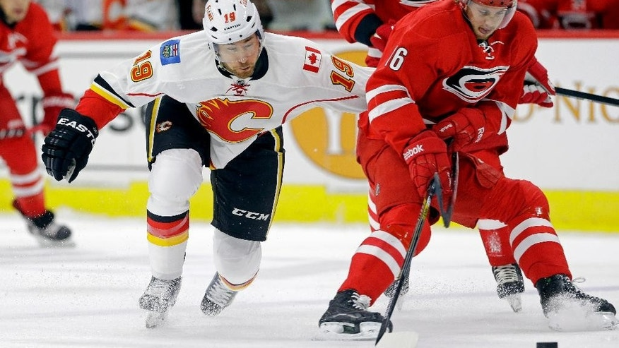 Calgary Flames' David Jones (19) and Carolina Hurricanes' Elias Lindholm (16), of Sweden, skate for the puck during the first period of an NHL hockey game in Raleigh, N.C., Monday, Nov. 10, 2014. (AP Photo/Gerry Broome)