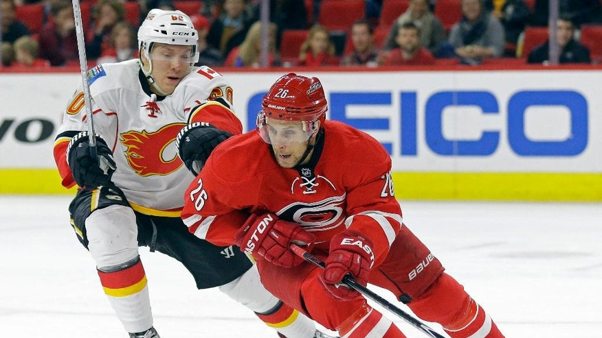 Carolina Hurricanes' John-Michael Liles (26) and Calgary Flames' Markus Granlund (60), of Finland, skate for the puck during the first period of an NHL hockey game in Raleigh, N.C., Monday, Nov. 10, 2014. (AP Photo/Gerry Broome)