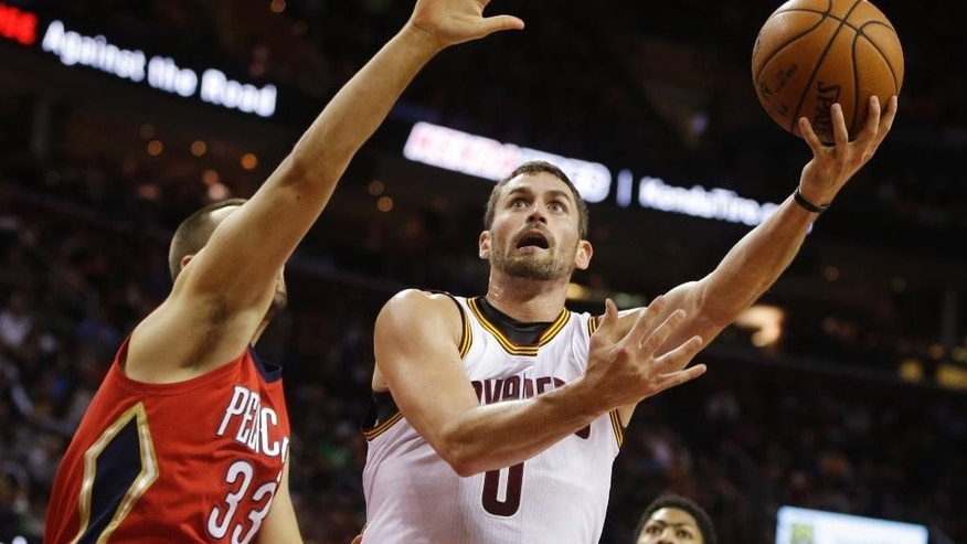 Cleveland Cavaliers' Kevin Love (0) shoots against New Orleans Pelicans' Ryan Anderson in the first quarter of an NBA basketball game Monday, Nov. 10, 2014, in Cleveland. (AP Photo/Mark Duncan)