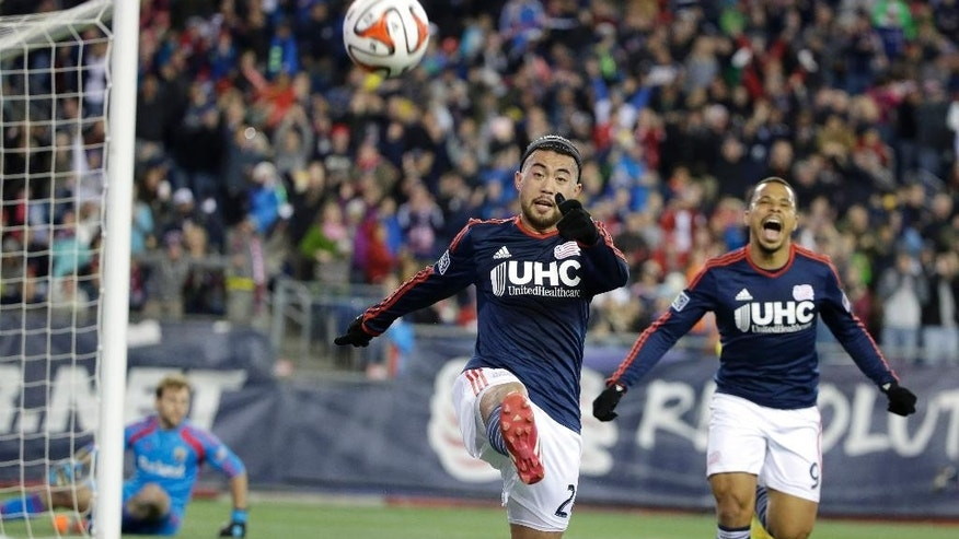 New England Revolution midfielder Lee Nguyen, center, kicks the ball as he celebrates his goal with forward Charlie Davies, right, as Columbus Crew goalkeeper Steve Clark, left, watches during the first half of an MLS playoff soccer game, Sunday, Nov. 9, 2014, in Foxborough, Mass. New England won 3-1, and advanced to the Eastern Conference finals. (AP Photo/Steven Senne)