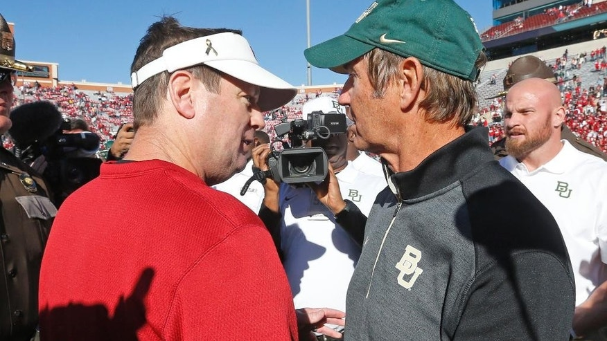 Oklahoma head coach Bob Stoops, left, and Baylor head coach Art Briles, right, shake hands following their NCAA college football game in Norman, Okla., Saturday, Nov. 8, 2014. Baylor won 48-14. (AP Photo/Sue Ogrocki)