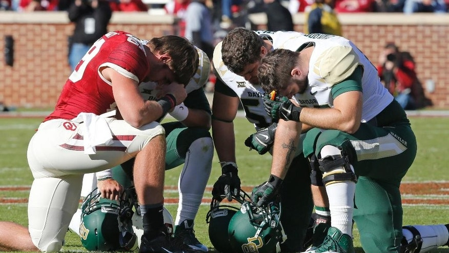 Oklahoma tight end Connor Knight, left, kneels with Baylor offensive tackle Spencer Drango, center, and offensive lineman Tyler Edwards, right, as injured Oklahoma quarterback Trevor Knight is attended to in the fourth quarter of an NCAA college football game in Norman, Okla., Saturday, Nov. 8, 2014. Baylor won 48-14. (AP Photo/Sue Ogrocki)