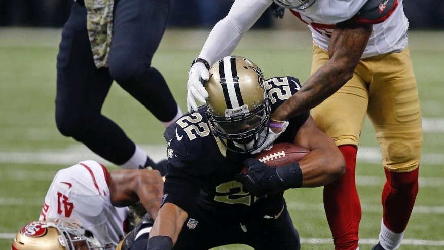 New Orleans Saints running back Mark Ingram (22) is tackled by San Francisco 49ers cornerback Chris Culliver (29) and strong safety Antoine Bethea (41) in the first half of an NFL football game in New Orleans, Sunday, Nov. 9, 2014. (AP Photo/Bill Haber)