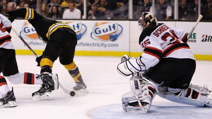 Boston Bruins center Seth Griffith, left, skates backwards as he pokes the puck between his legs, which then slid through the pads of New Jersey Devils goalie Cory Schneider (35) for a goal during the second period of an NHL hockey game in Boston, Monday, Nov. 10, 2014. (AP Photo/Charles Krupa)