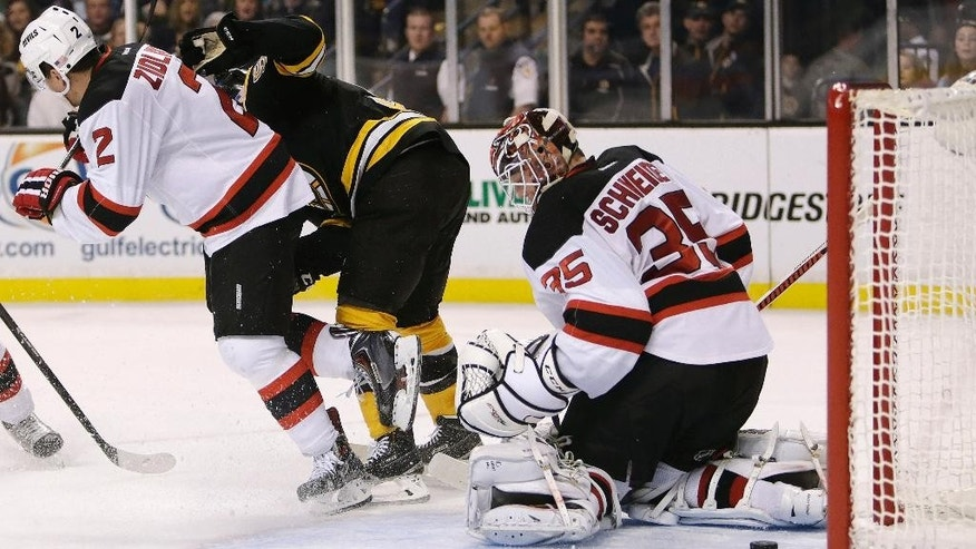 The puck slides through the pads of New Jersey Devils goalie Cory Schneider (35) for a goal on a shot through the legs of Boston Bruins center Seth Griffith, center, during the second period of an NHL hockey game in Boston, Monday, Nov. 10, 2014. At left is New Jersey Devils defenseman Marek Zidlicky. (AP Photo/Charles Krupa)