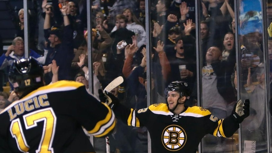 Boston Bruins center Seth Griffith, right, celebrates his goal against New Jersey Devils goalie Cory Schneider during the second period of an NHL hockey game in Boston, Monday, Nov. 10, 2014. (AP Photo/Charles Krupa)