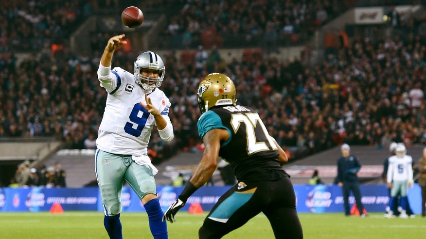 Dallas Cowboys quarterback Tony Romo (9) pass the ball to tight end Jason Witten (82) as Jacksonville Jaguars cornerback Dwayne Gratz (27) defends during the first half of an NFL football game at Wembley Stadium, London, Sunday, Nov. 9, 2014. (AP Photo/Tim Ireland)
