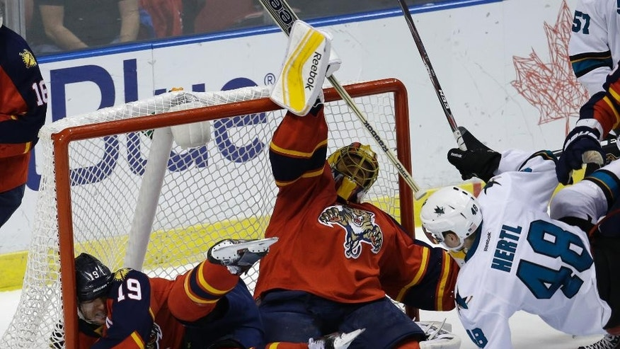 San Jose Sharks center Tomas Hertl (48) commits a roughing penalty as Florida Panthers right wing Scottie Upshall (19) falls into the net with goalie Roberto Luongo, center, in the second period of an NHL hockey game, Tuesday, Nov. 11, 2014, in Sunrise, Fla. (AP Photo/Lynne Sladky)