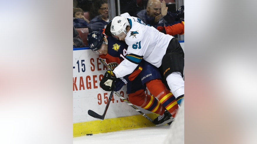 Florida Panthers left wing Tomas Fleischmann (14) and San Jose Sharks defenseman Justin Braun (61) go for the puck in the first period of an NHL hockey game, Tuesday, Nov. 11, 2014, in Sunrise, Fla. (AP Photo/Lynne Sladky)