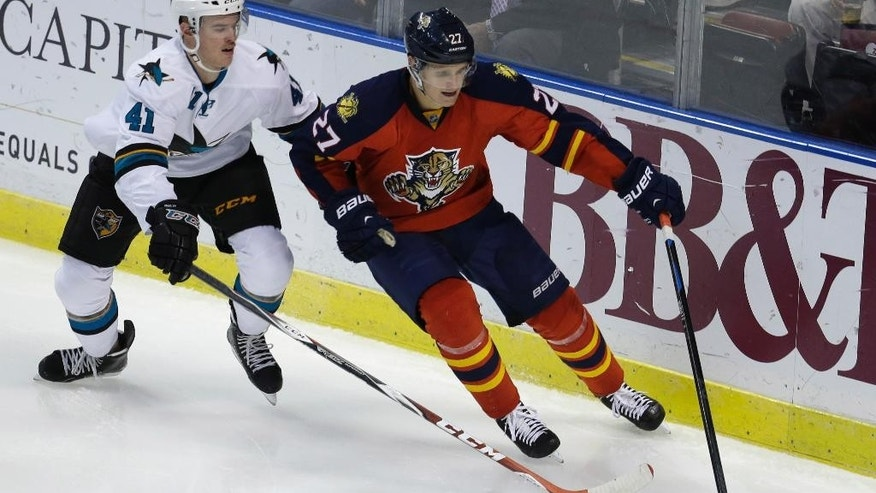 San Jose Sharks defenseman Mirco Mueller (41) and Florida Panthers center Nick Bjugstad (27) go for the puck in the second period of an NHL hockey game, Tuesday, Nov. 11, 2014, in Sunrise, Fla. (AP Photo/Lynne Sladky)