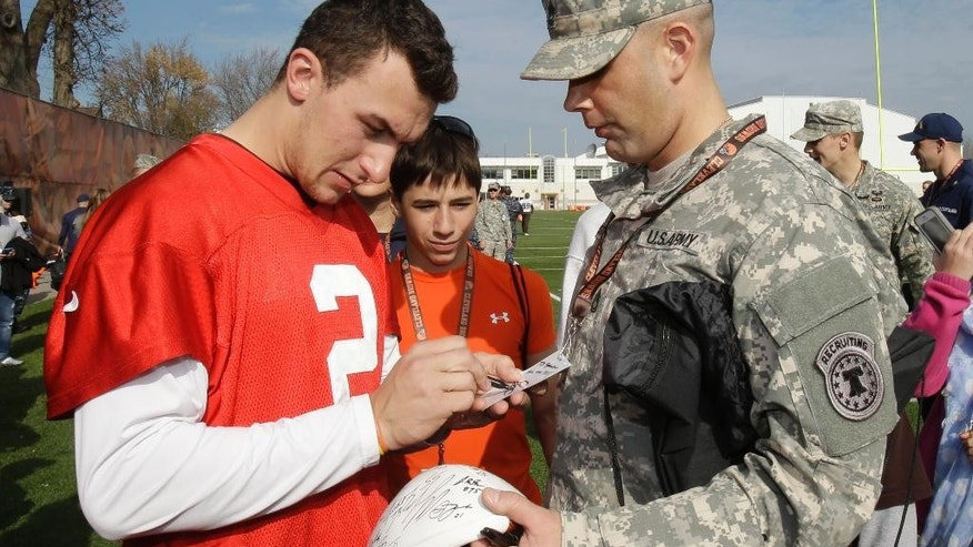 Cleveland Browns quarterback Johnny Manziel, left, signs an autograph for Joe Starcher, with the U.S. Army, after practice at the NFL football team's training camp Tuesday, Nov. 11, 2014, in Berea, Ohio. As part of the Salute to Service campaign, military guests representing all five branches of the military were able to watch the Browns practice on Veteran's Day. (AP Photo/Tony Dejak)