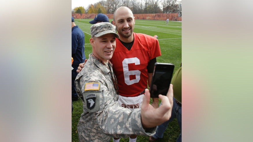 Jeremy King, with the U.S. Army, takes a selfie with Cleveland Browns quarterback Brian Hoyer, right, after watching the Browns practice at the NFL football team's training camp Tuesday, Nov. 11, 2014, in Berea, Ohio. As part of the Salute to Service campaign, military guests representing all five branches of the military were able to watch the Browns practice on Veterans Day. (AP Photo/Tony Dejak)